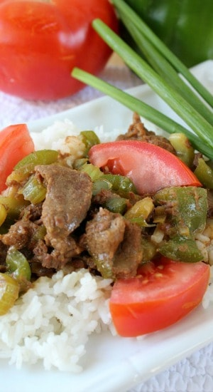 Green Pepper Steak with rice on a white plate with green onions, a bell pepper, and a tomato in the background.