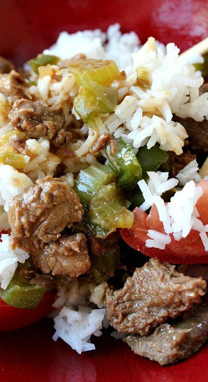 A close up photo of a red bowl with rice, beef, bell peppers, and tomato.