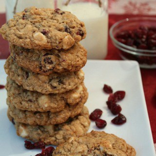 Oatmeal Craisin White Chocolate Chip Cookies stacked up on a white plate with craisins on the plate and a glass bowl of craisins in the background.