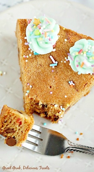 a slice of chocolate chip cookie cake with a bite on a fork.