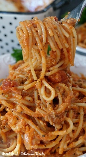 A forkful of Italian Sausage Spaghetti Bake being held up over a white bowl filled with the spaghetti bake.