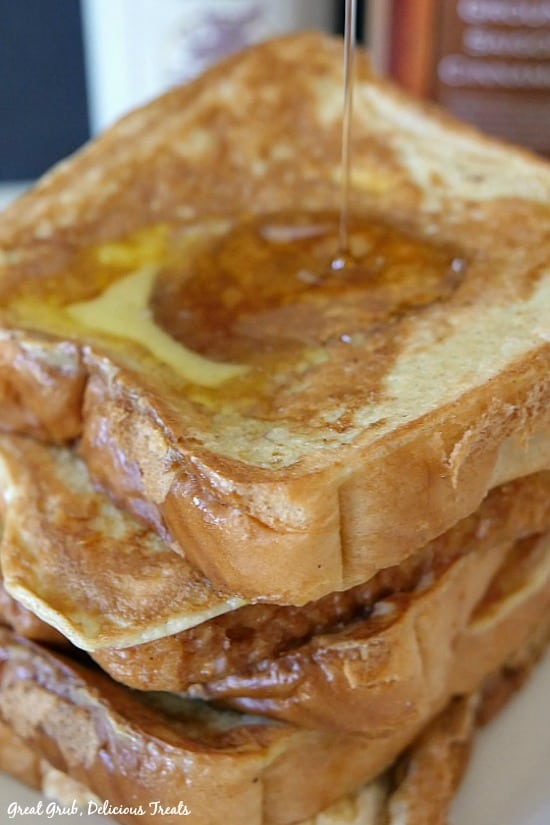 A stack of Texas Style French Toast with melted butter and maple syrup being drizzled over them.