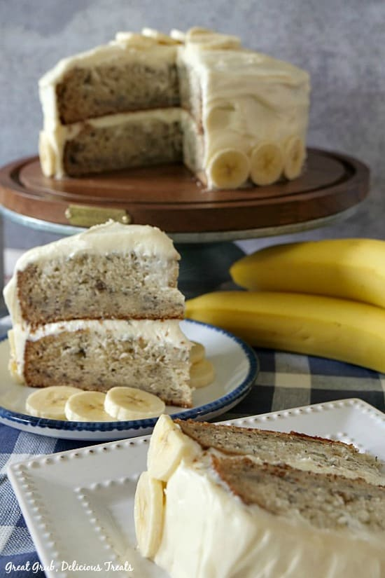 Banana Cake with Cream Cheese Frosting is a display of the cake on a cake stand, and two pieces cut and on plates with bananas in the background