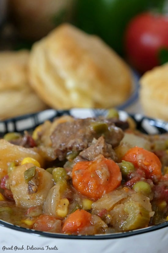 Slow Cooker Beef Stew is in a white and black bowl loaded with beef stew with biscuits in the background.