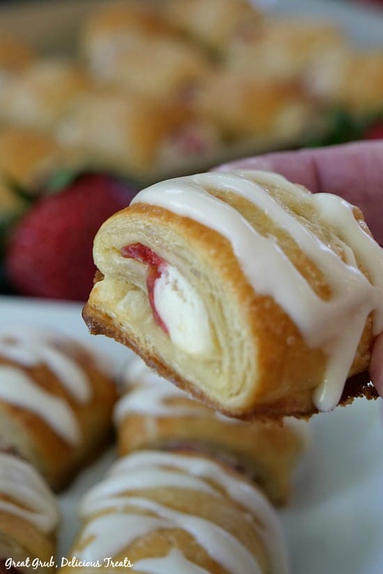 Mini Strawberry Strudel Bites is a finished strudel bite being held and shown close up to the camera showing the filling inside the pastry.