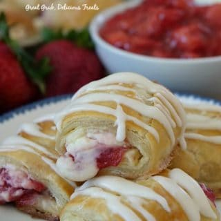 Strawberry cream cheese filled pastry strudels stacked on a plate drizzled with icing.
