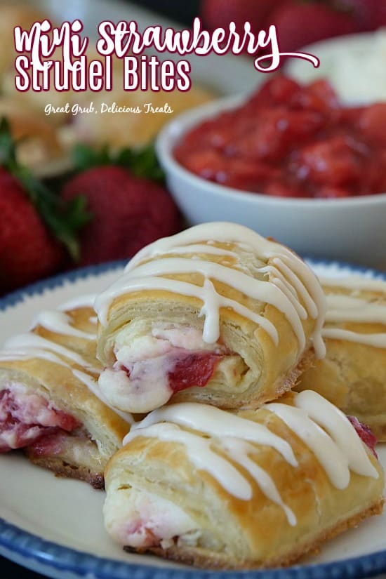 Mini Strawberry Strudel Bites are stacked in a plate with blue trim with strawberry filling in a bowl and fresh strawberries beside the plate.