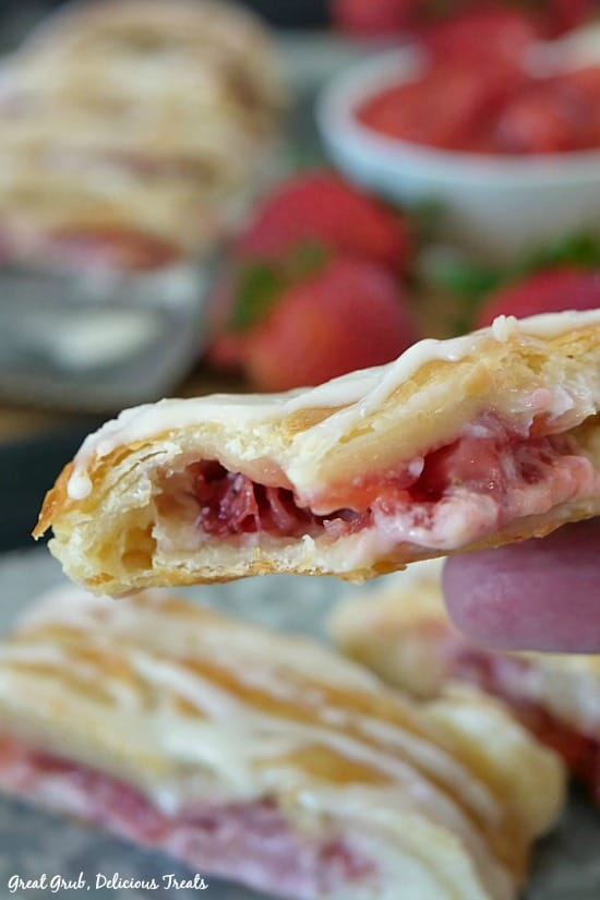 A slice of Strawberry Cream Cheese Danish being held showing the strawberry filling.