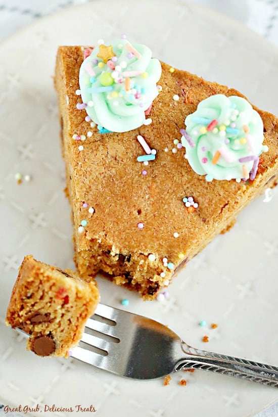 Chocolate Chip Cookie Cake - a pie shaped wedge of chocolate chip cookie with a bite on a fork, sitting on a white plate.