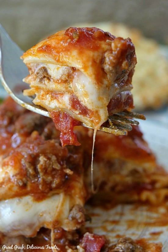 Best Homemade Lasagna - this is a bite of lasagna on a fork being held up over the piece of lasagna that is on a white plate.