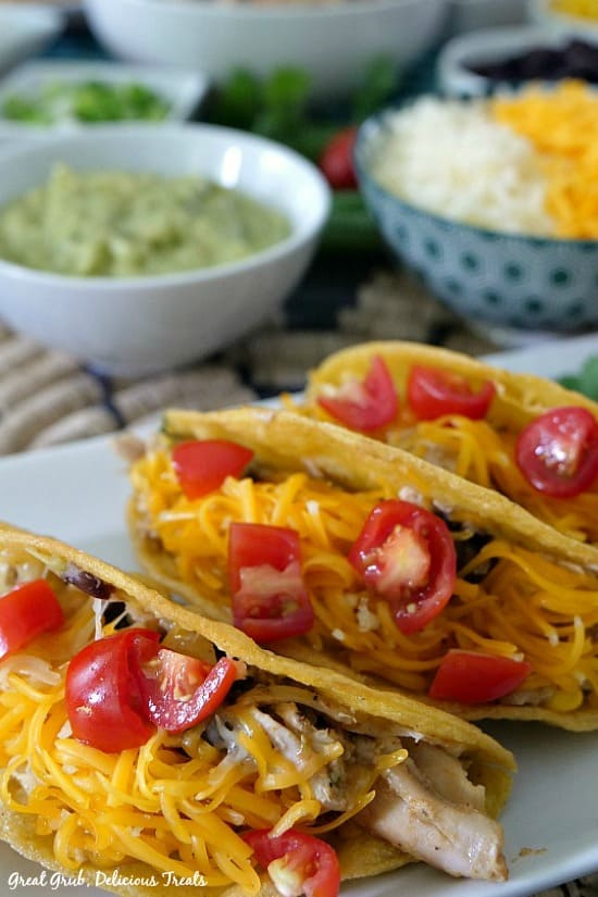 Southwest Rotisserie Chicken Tacos has 3 tacos laying on a white plate with guacamole, cheese, green onions in bowls in the background.