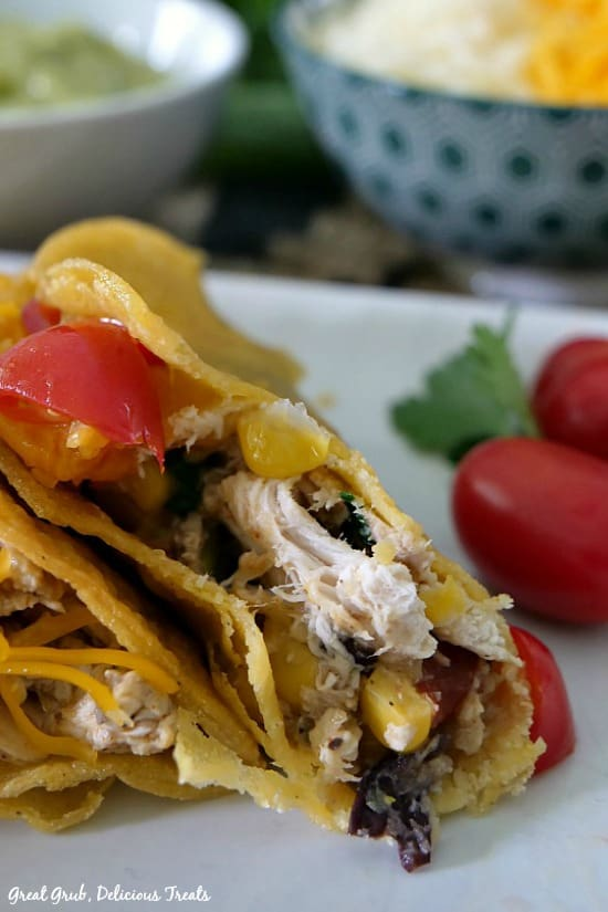 Southwest Rotisserie Chicken Tacos is a half eaten taco with chicken, corn, black beans and tomatoes sitting on a white plate with cheese and tomatoes in the background.