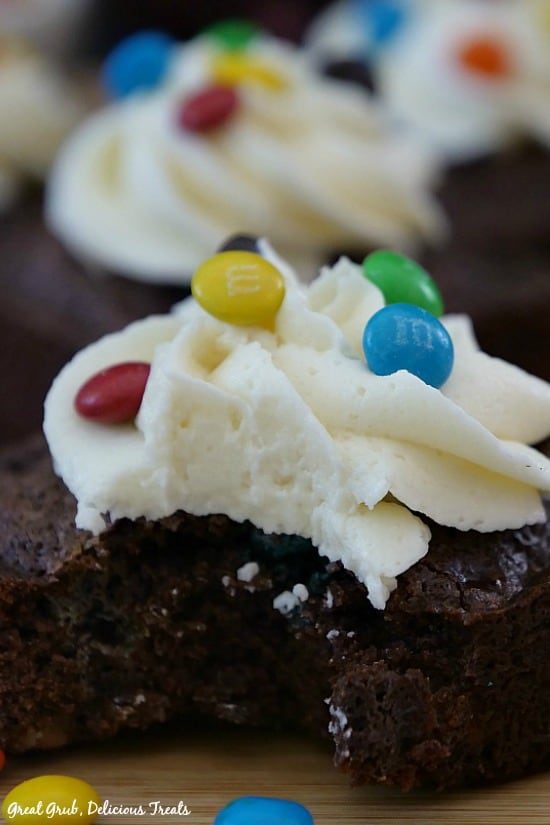 Chocolaty Brownies - A brownie topped with buttercream frosting and mini M&Ms with a bite taken out.
