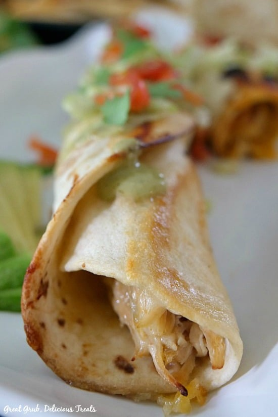 Spicy Chicken Flautas - one single chicken flauta wrapped in a flour tortilla showing the chicken mixture peeking out of the end of the tortilla, garnished with a little shredded lettuce, diced tomatoes.