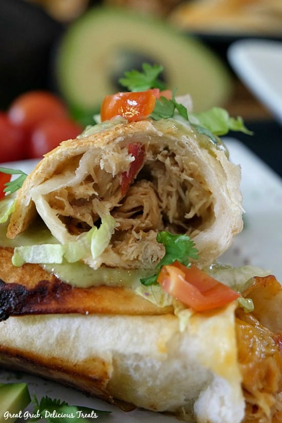 Spicy Chicken Flautas - photo of a flauta and the inside chicken mixture leaning on the other flauta, both garnished with diced tomatoes and shredded lettuce.