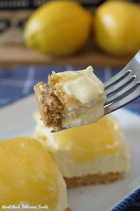 Lemonade Cheesecake Bars - a bite of lemon cheesecake on a fork with two cheesecake bars on a white plate with two lemons in the background.