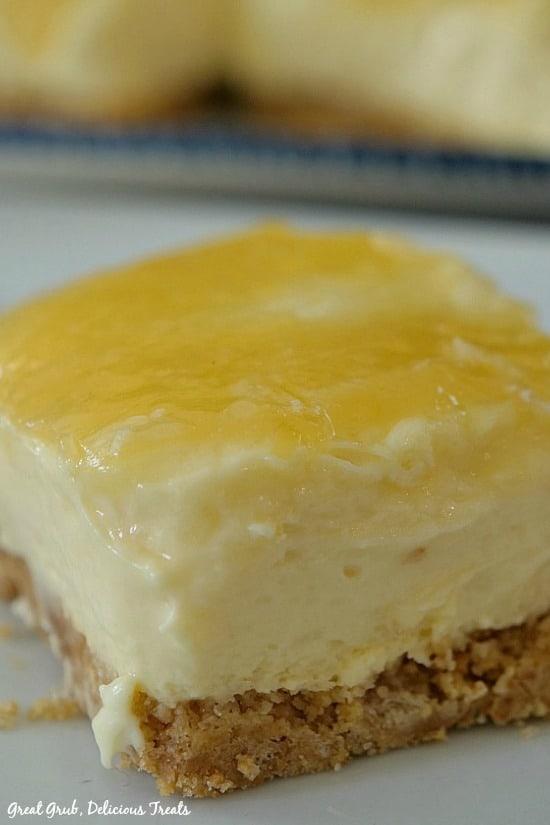 Lemonade Cheesecake Bars - a photo of one lemon cheesecake bar on a white plate with lemon glaze on top.