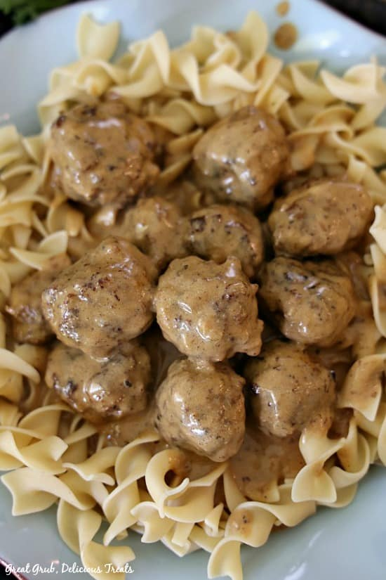 A dozen Swedish Meatballs with gravy served over egg noodles placed in a light blue bowl