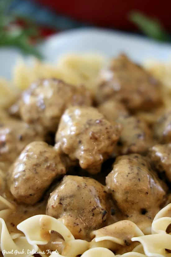 Swedish Meatballs with a gravy sauce sitting on a bed of egg noodles in a light blue bowl.