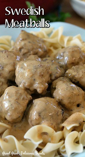 A close up view of Swedish Meatballs and gravy over egg noodles in a light blue bowl.