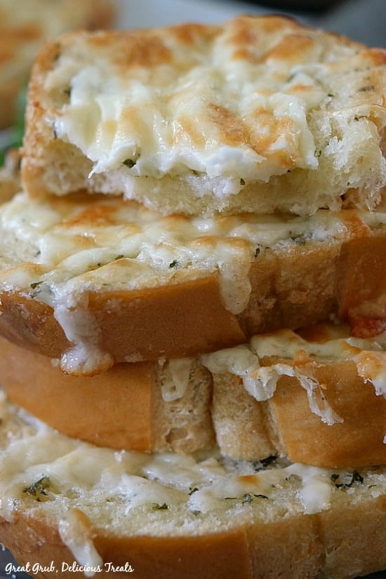 Cheesy Garlic Cheese Toast is a stack of cheese toast piled on top of each other showing the melted cheese.