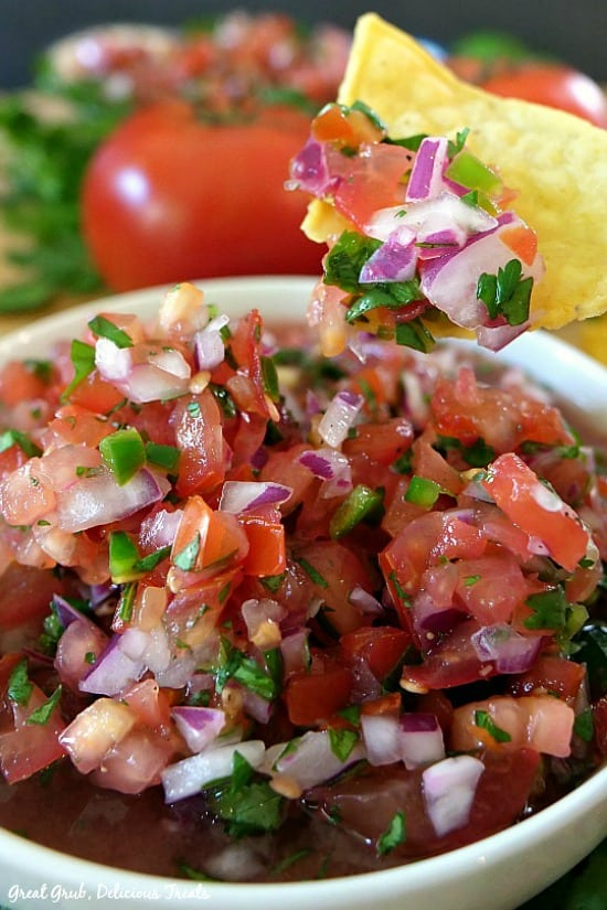 Pico de Gallo - a white bowl full of homemade salsa with some chunky salsa on a tortilla chip.