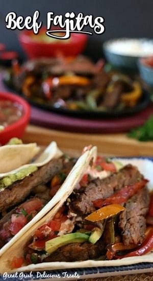 Beef Fajitas - Fajitas stuffed in warm tortillas with sizzling fajitas in the background.