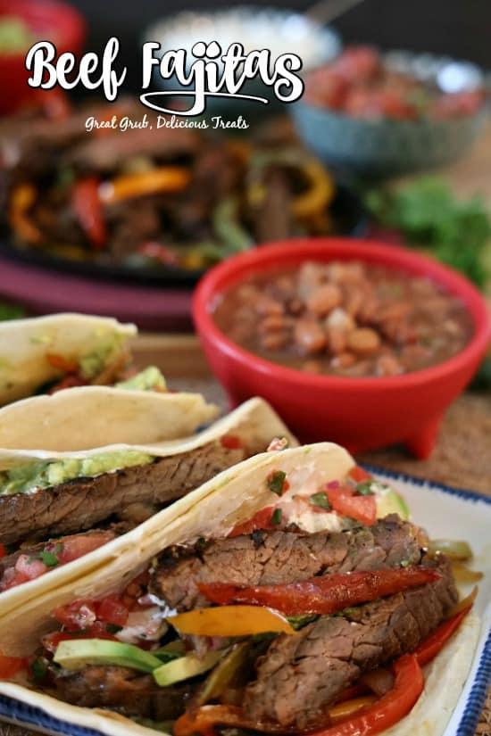 Beef Fajitas - Photo of 3 fajitas on a white plate with sizzling fajitas, beans, pico de gallo in the background.