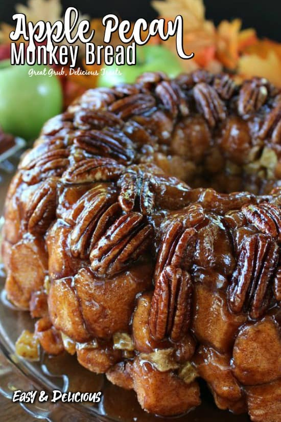 Apple Pecan Monkey Bread made in a Bundt pan, placed on a glass plate, with whole pecans layered on top with green apples and fall foliage in the background.