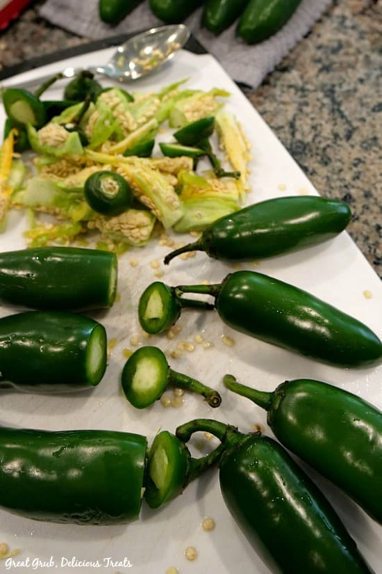White cutting board with 7 jalapenos with stems cut off and seeds removed.
