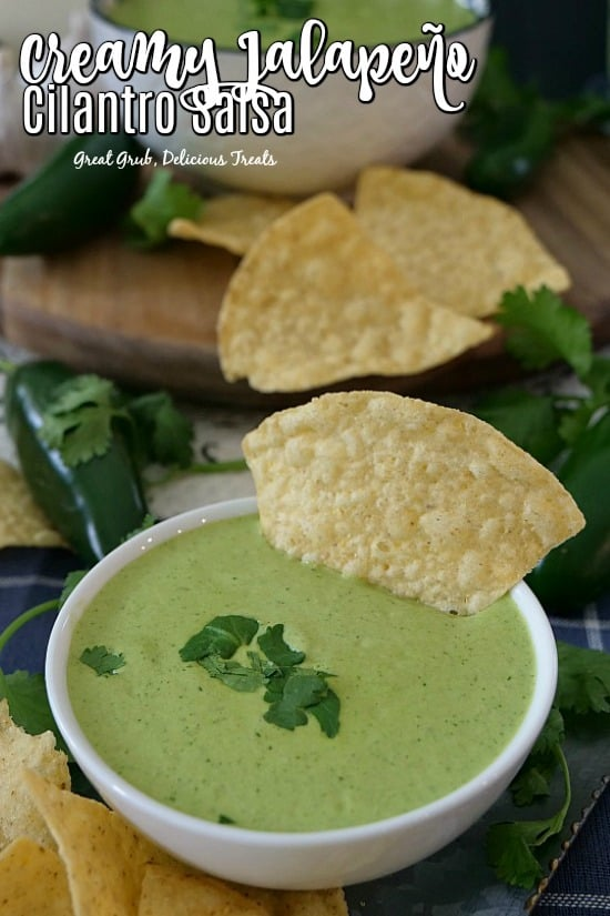 Creamy Jalapeno Cilantro Salsa - a white bowl filled with this salsa with a tortilla chip dipped in the bowl with jalapenos, cilantro and chips in the background.
