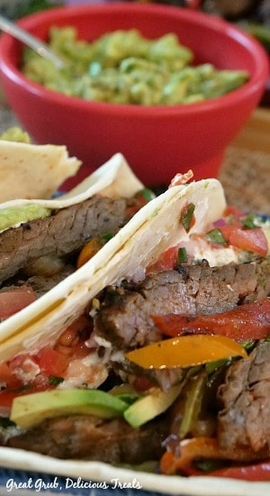 Beef Fajitas - 3 beef fajitas on a plate with beef, peppers and onions stuffed in warm tortillas with a bowl of guacamole in the background.