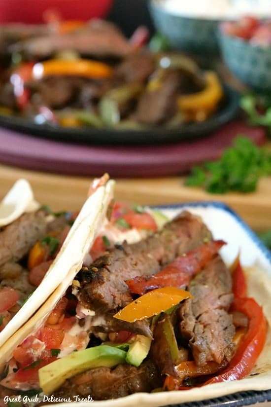 Beef fajitas - fajita meat with peppers and onions stuffed in flour tortillas with sizzling fajitas in the background.