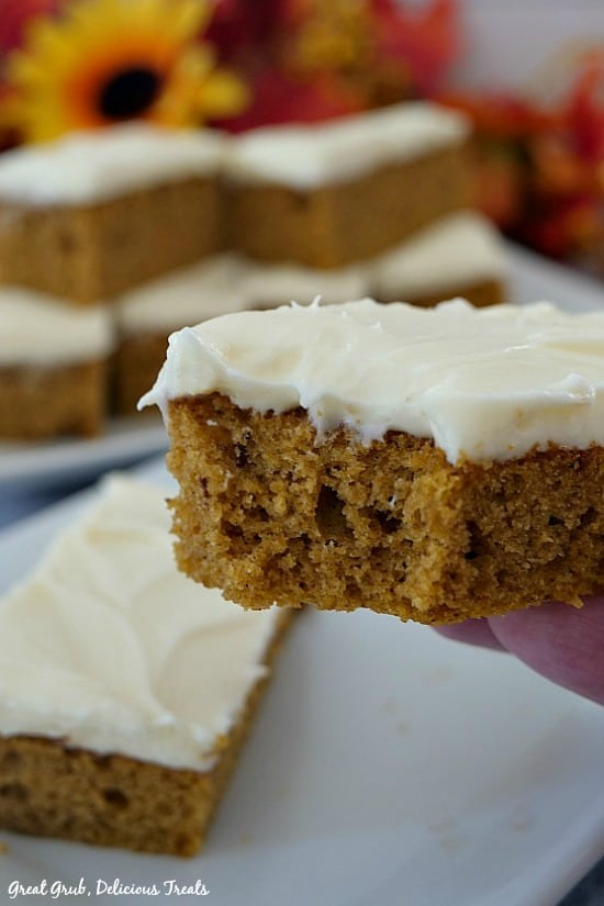 Pumpkin Bars with Cream Cheese Frosting - pumpkin bar being held up showing a bite taking out with bars on a white plate in the background with fall flowers in the background as well.