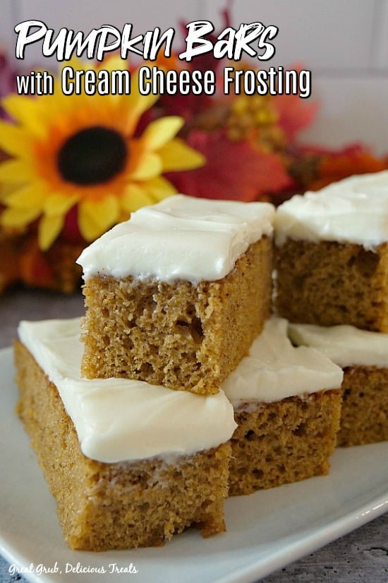 Pumpkin Bars with Cream Cheese Frosting - 5 pumpkin bars on top of a white plate with fall flowers in the background, even a sunflower.
