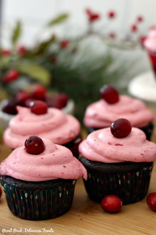 Chocolate Cupcakes with Cranberry Buttercream Frosting sitting on a wood surface with cranberries and pine foliage in the background.