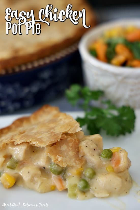 A slice of chicken pot pie on a white plate with a small white bowl filled with mixed veggies in the background next to a blue pie pan filled with chicken pot pie.
