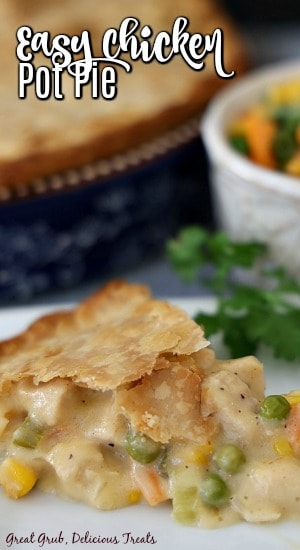 A slice of chicken pot pie on a white plate, garnished with parsely with a blue pie pan filled with pot pie in the background next to a small white bowl filled with mixed veggies.