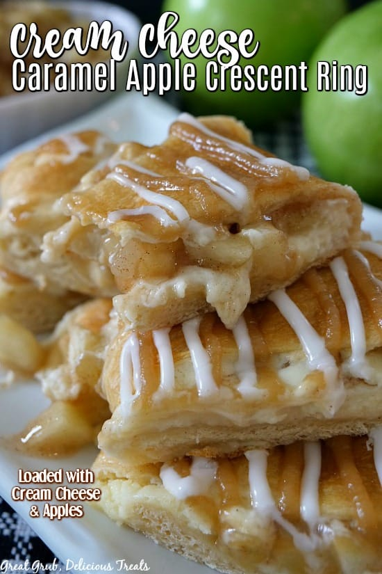 Cream Cheese Caramel Apple Crescent Ring - Sliced crescents filled with cream cheese and apples piled on each other and sitting on a white plate with two green apples in the background.