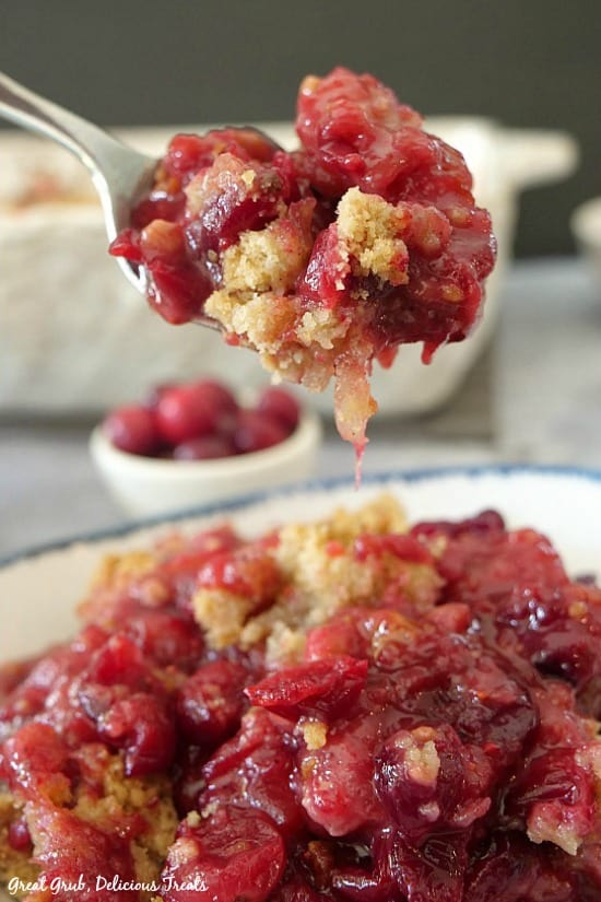 A spoonful of cranberry apple crisp being held over a bowl of crisp with cranberries in the background.
