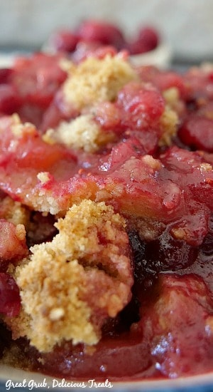 Close up picture of cranberry apple crisp showing the crisp topping and the fruit and juices in a white bowl.