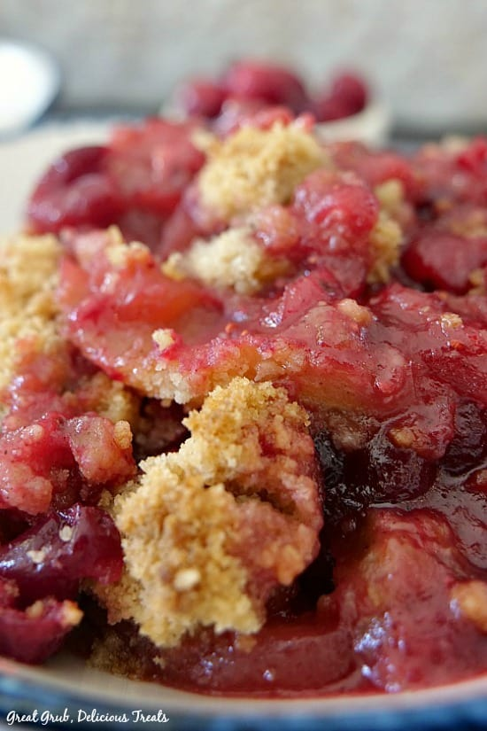 A close up of cranberry apple crisp showing the crisp topping and the fruit and juices in a white bowl with blue trim.