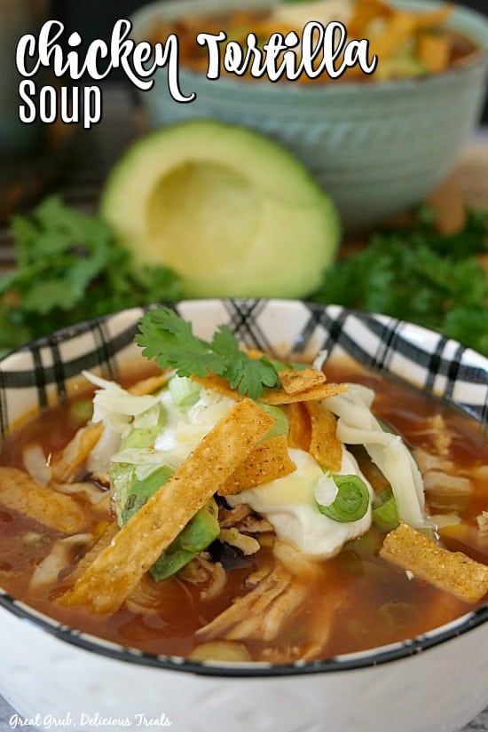 Best Chicken Tortilla Soup is in a white and black bowl, with tortilla strips, sour cream, cilantro on top with half an avocado and another bowl of soup in the background.