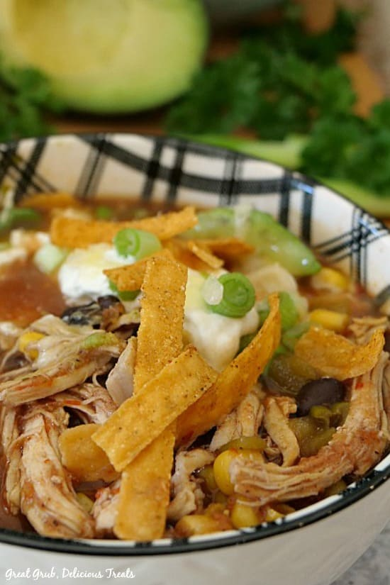 Best Chicken Tortilla Soup - a white and black bowl filled with soup and topped with tortilla strips, sour cream, green onions and avocados.