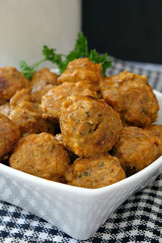 Turkey meatballs in a small white bowl with a plaid placemat underneath with parsley for decoration in the background.