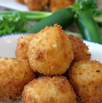 Mashed Potato balls on a white plate with jalapeños in the background