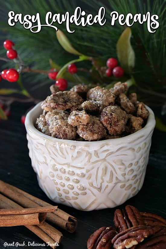 Candied pecans in a white bowl with cinnamon sticks and whole pecans in the foreground with green folage in the background.