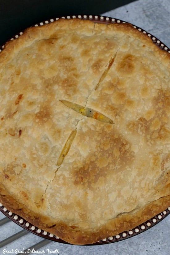 A whole pot pie in a pie pan with brown and white trim, uncut with 3 small slices on top of crust.
