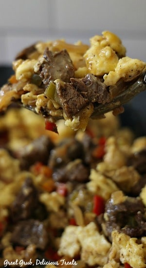 A close up photo of beef fajita breakfast scramble consisting of eggs, peppers, and beef on a fork.