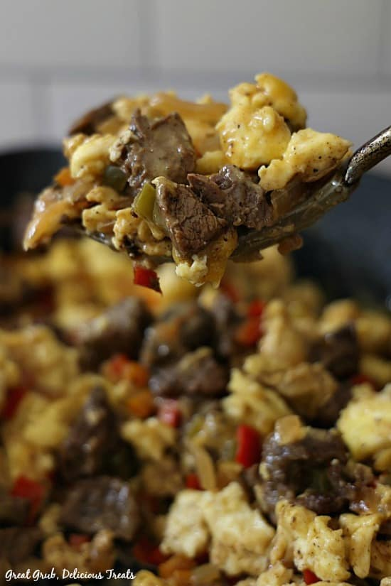 A photo of a bite of beef fajita breakfast scramble being held up above a skillet filled with the recipe, showing fajita meat, scrambled eggs, peppers and onions and cheese.